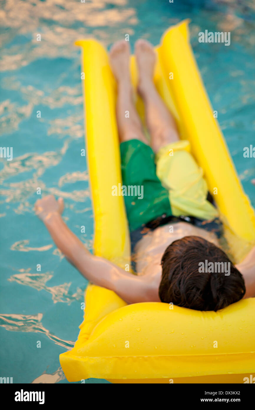 Boy laying on yellow inflatable raft in swimming pool, high angle view - Stock Image