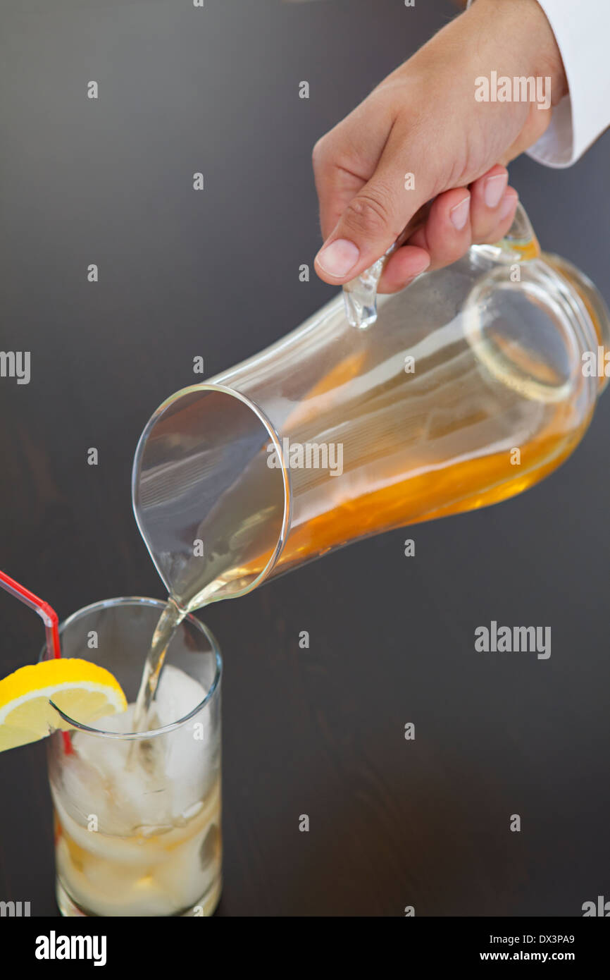 Man's hand pouring iced tea from pitcher into glass with lemon wedge on black background, high angle view, close - Stock Image