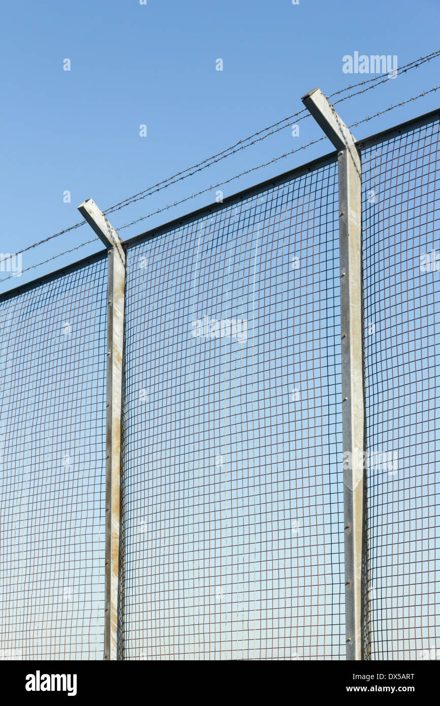 Tall wire mesh security fence on concrete posts, topped with three ...