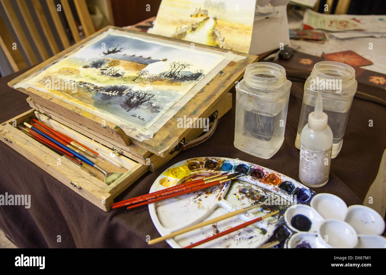 a-watercolour-painting-on-a-table-easel-with-a-palette-brushes-and-DX67M1.jpg