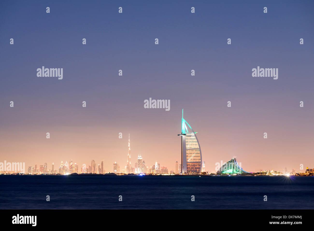 Night skyline across sea to luxury Burj al Arab hotel and city of Dubai with Burj Khalifa tower in distance United - Stock Image