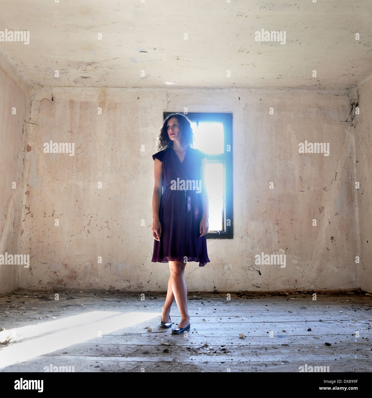 Woman standing by the window - Stock Image