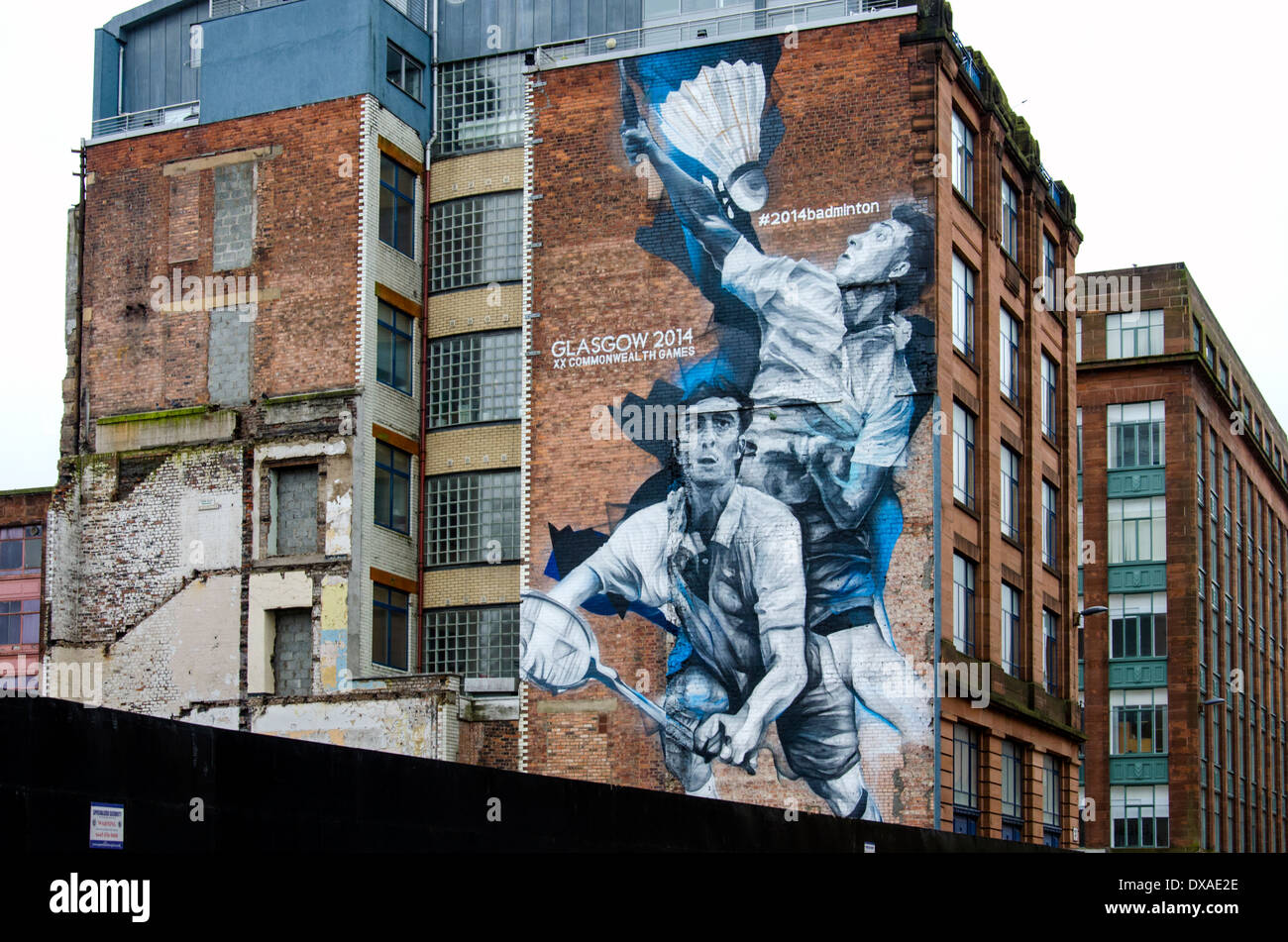 A mural depicting two badminton players on a building in Glasgow city centre advertising the 2014 Commonwealth Games. - Stock Image