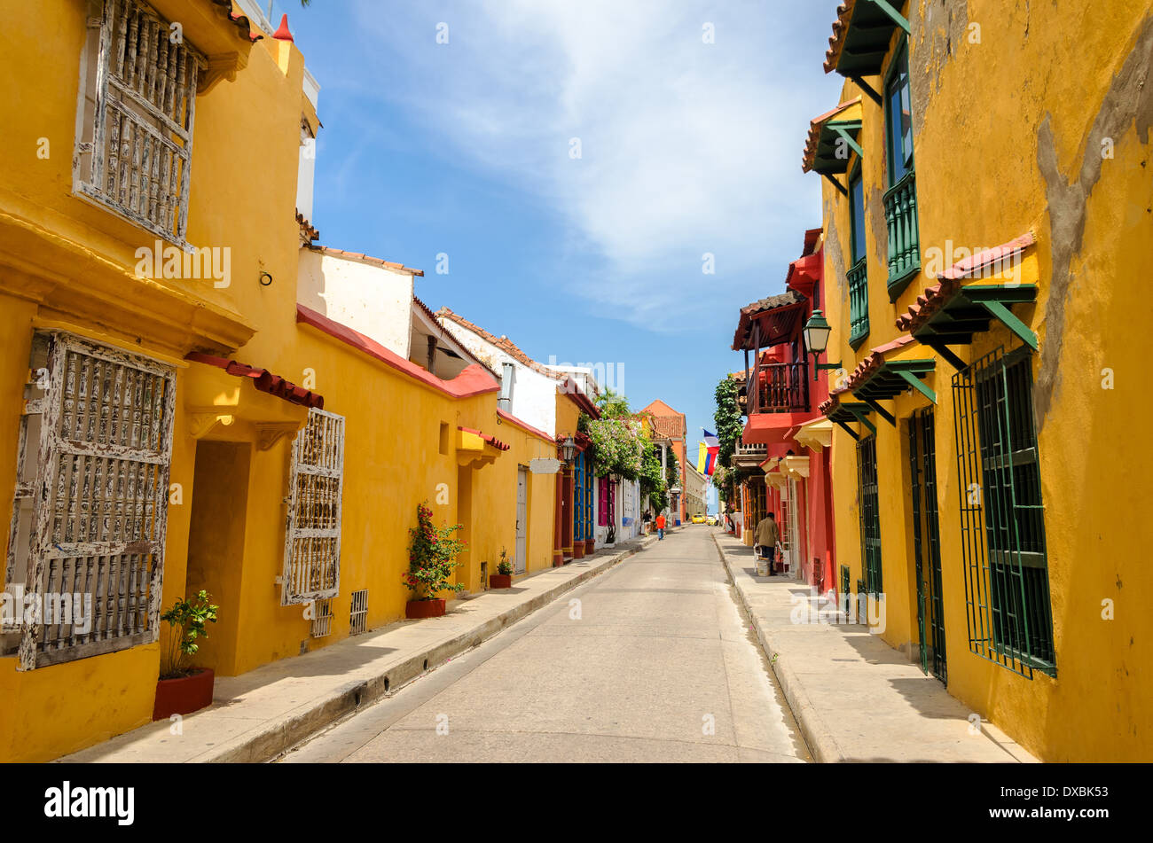 Typical street scene in Cartagena, Colombia of a street with old historic colonial houses on each side of it - Stock Image