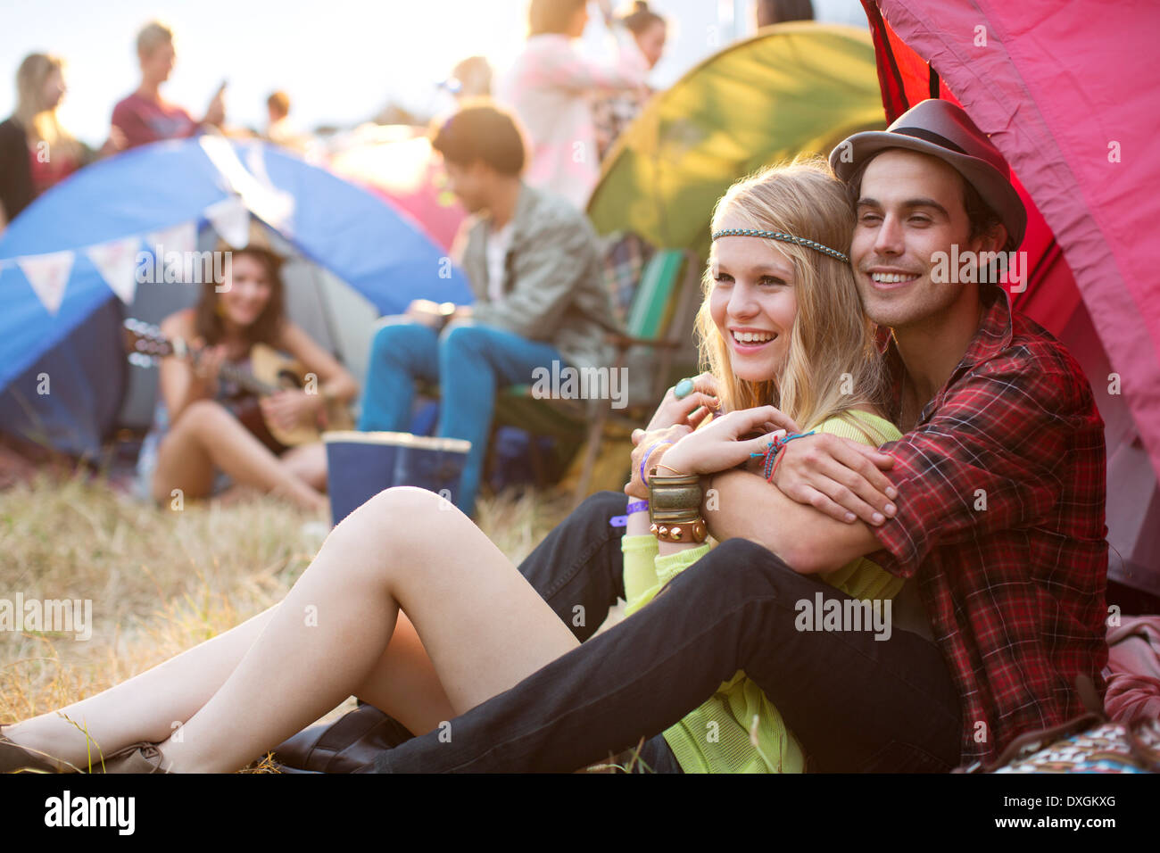 Couple hugging outside tent at music festival - Stock Image
