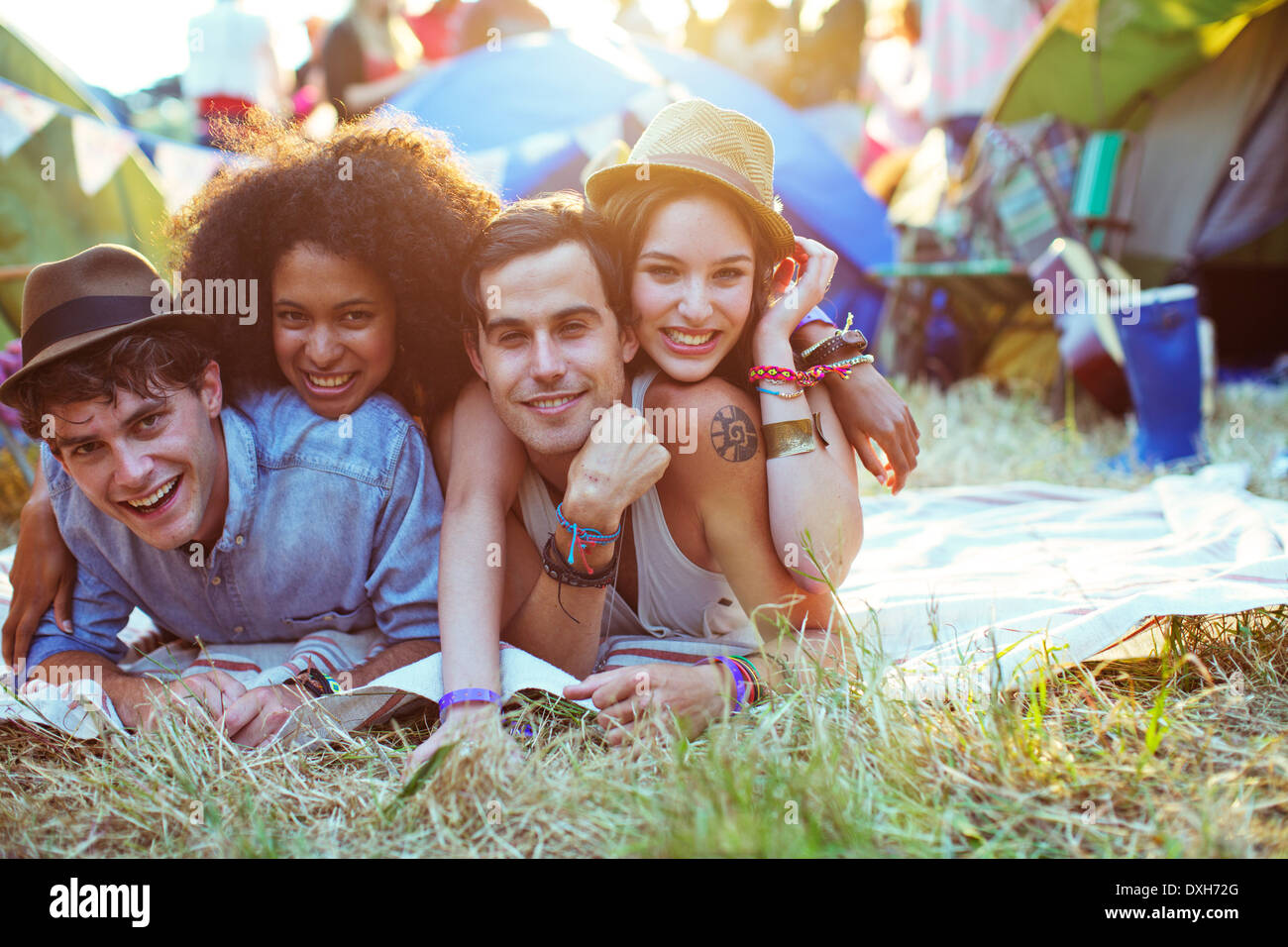 Portrait of friends laying on blanket outside tents at music festival - Stock Image