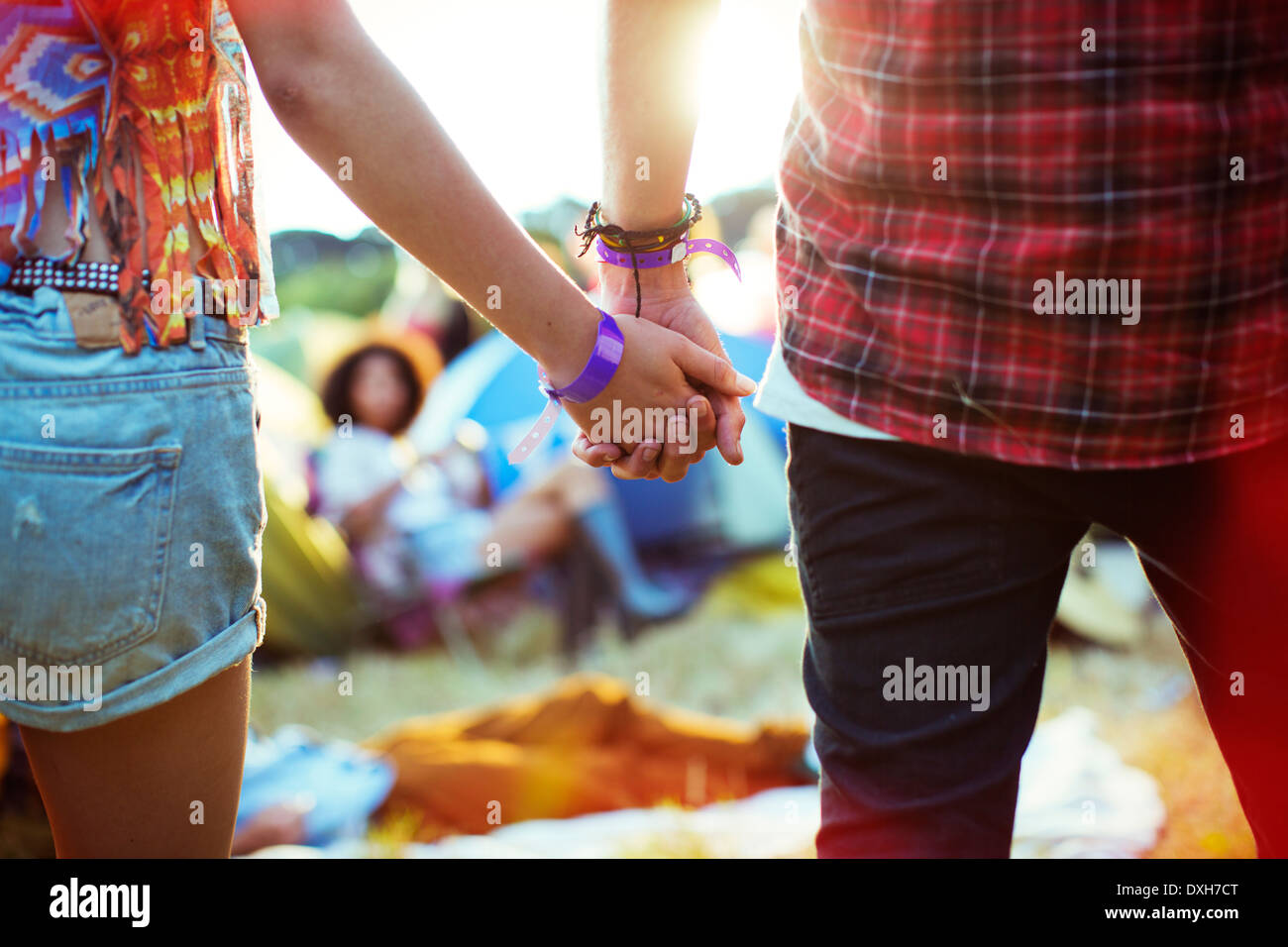 Close up of couple holding hands outside tents at music festival - Stock Image
