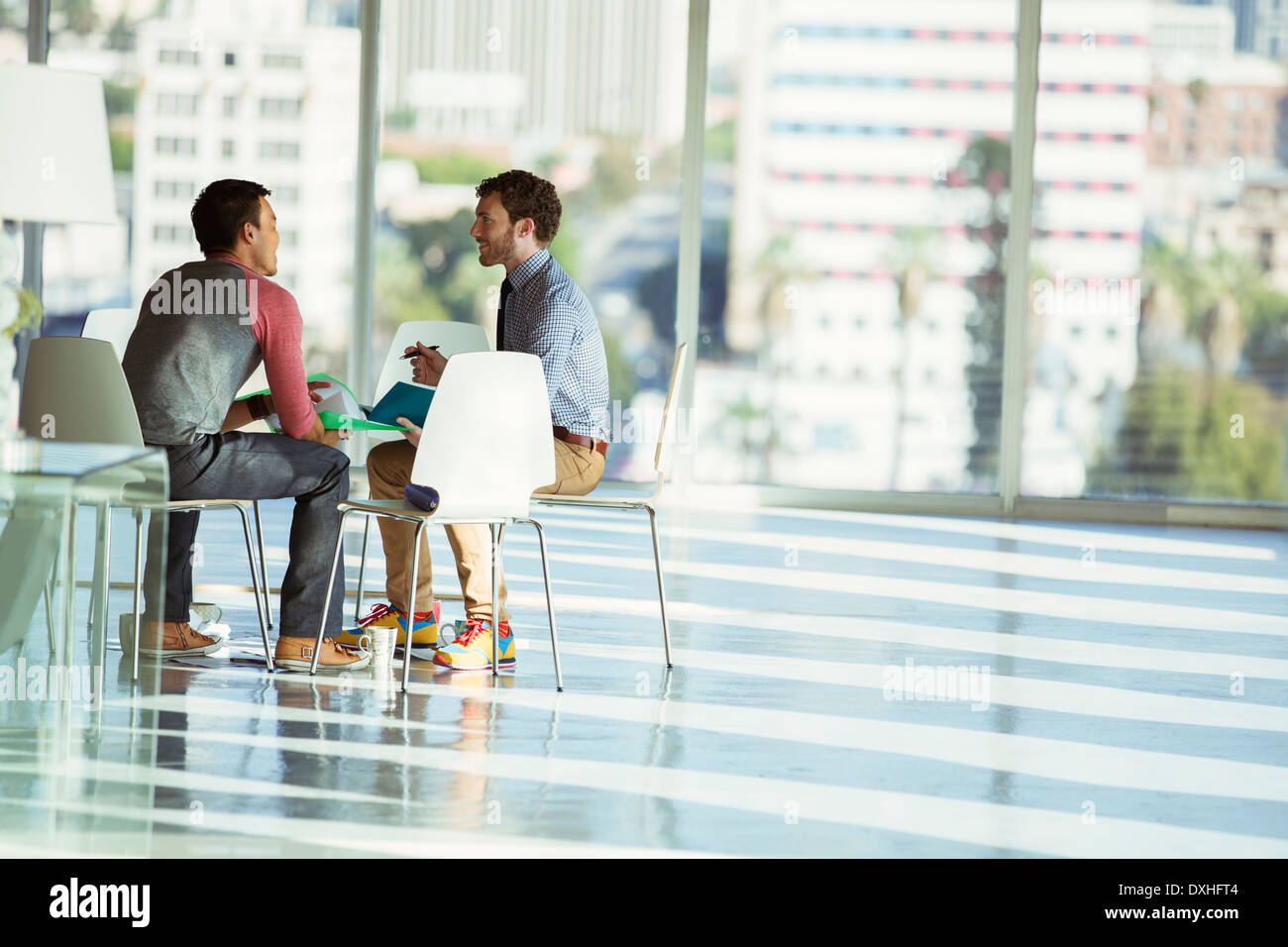 Creative businessmen meeting at circle of chairs in sunny office - Stock Image