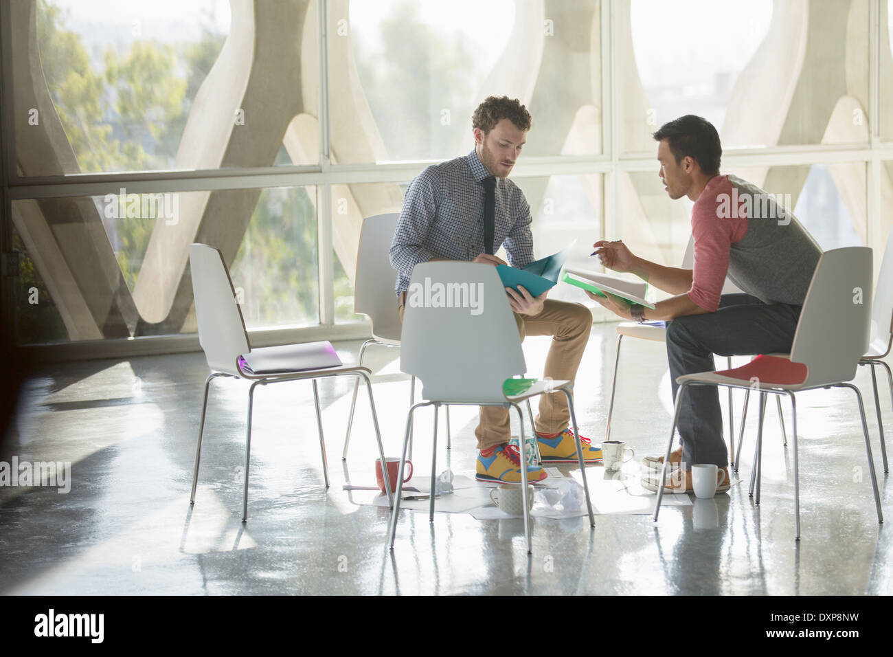 Creative businessmen brainstorming in circle of chairs - Stock Image