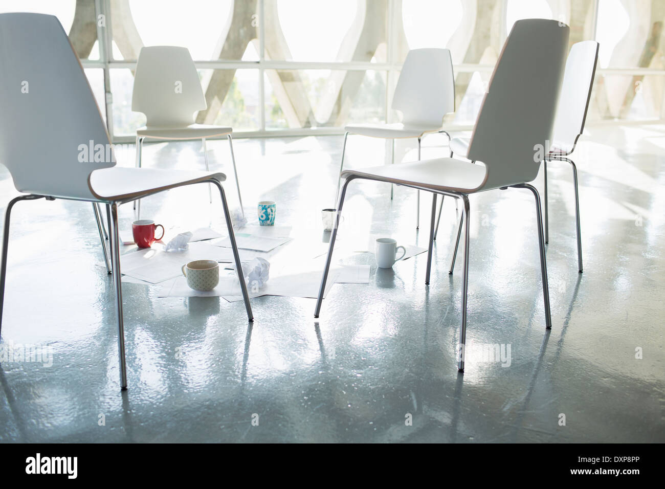 Coffee cups and paperwork at circle of chairs - Stock Image