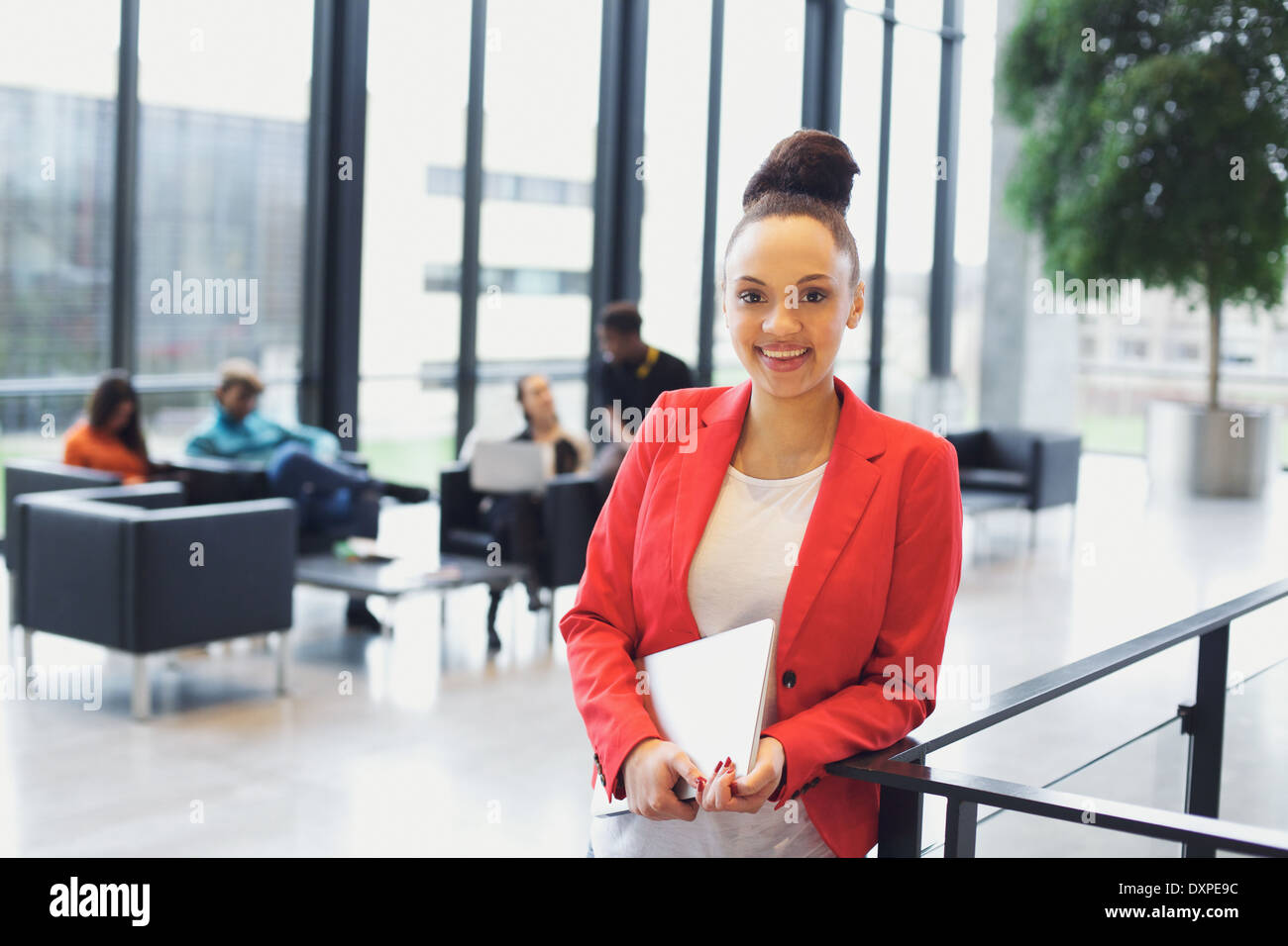Pretty young woman holding a laptop standing by a railing looking at camera smiling. Young African-American businesswoman. - Stock Image