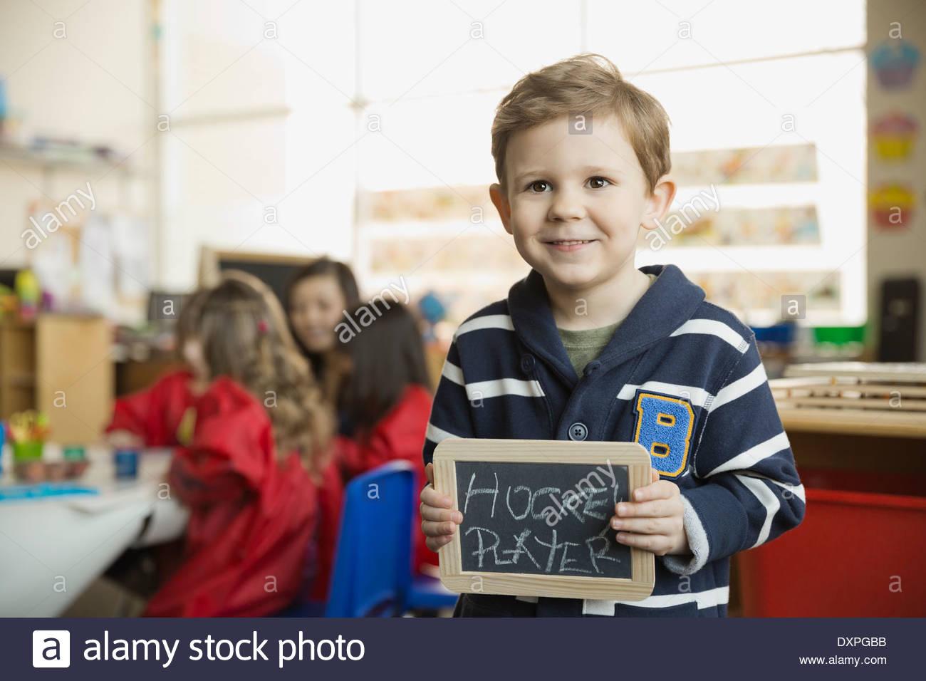 Elementary boy holding slate with 'Hockey Player' written on it - Stock Image