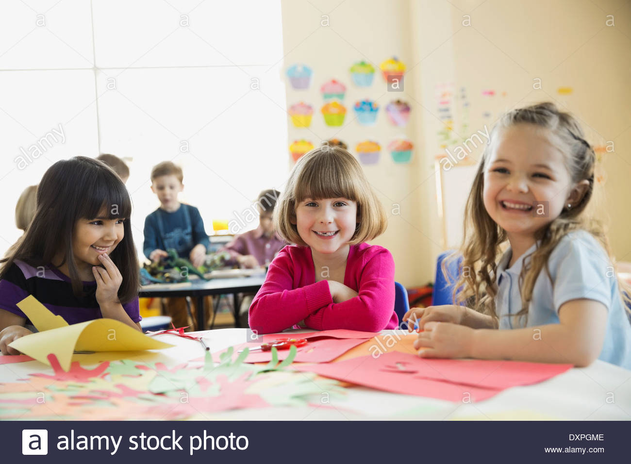 Smiling girls sitting at table in elementary class - Stock Image