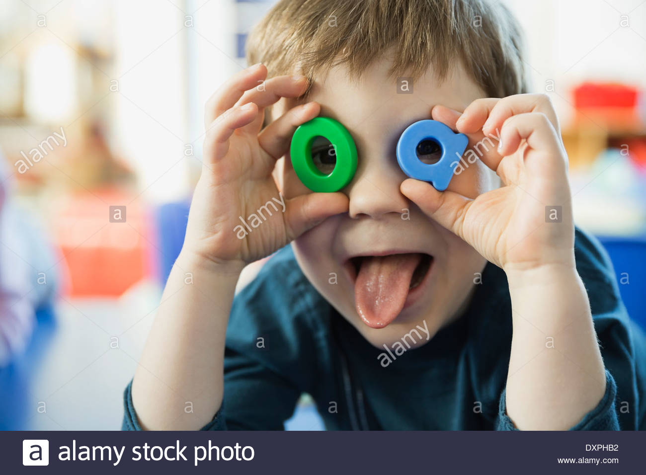 Playful boy making faces with letters - Stock Image