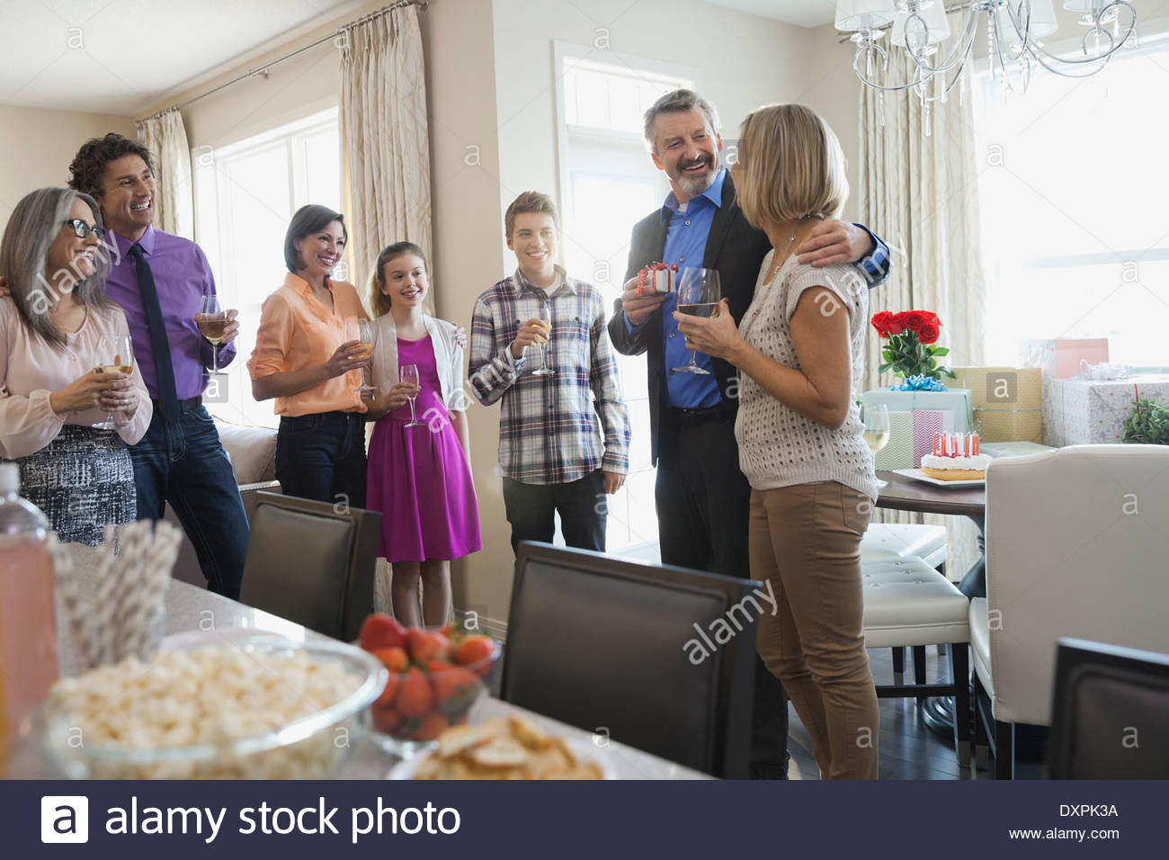 Family and friends enjoying drinks at birthday party - Stock Image
