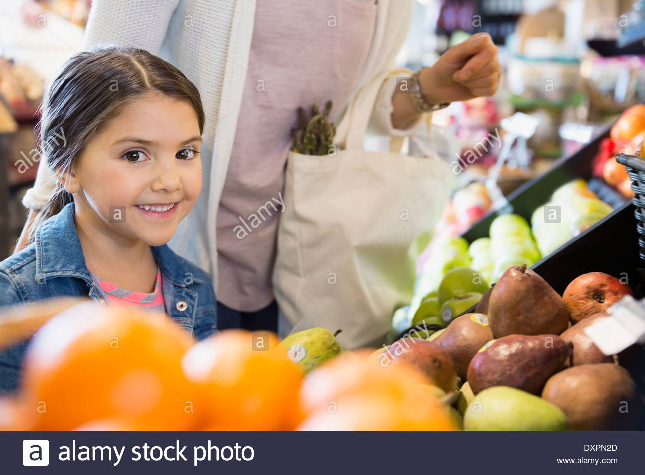Portrait of girl shopping for produce in market - Stock Image