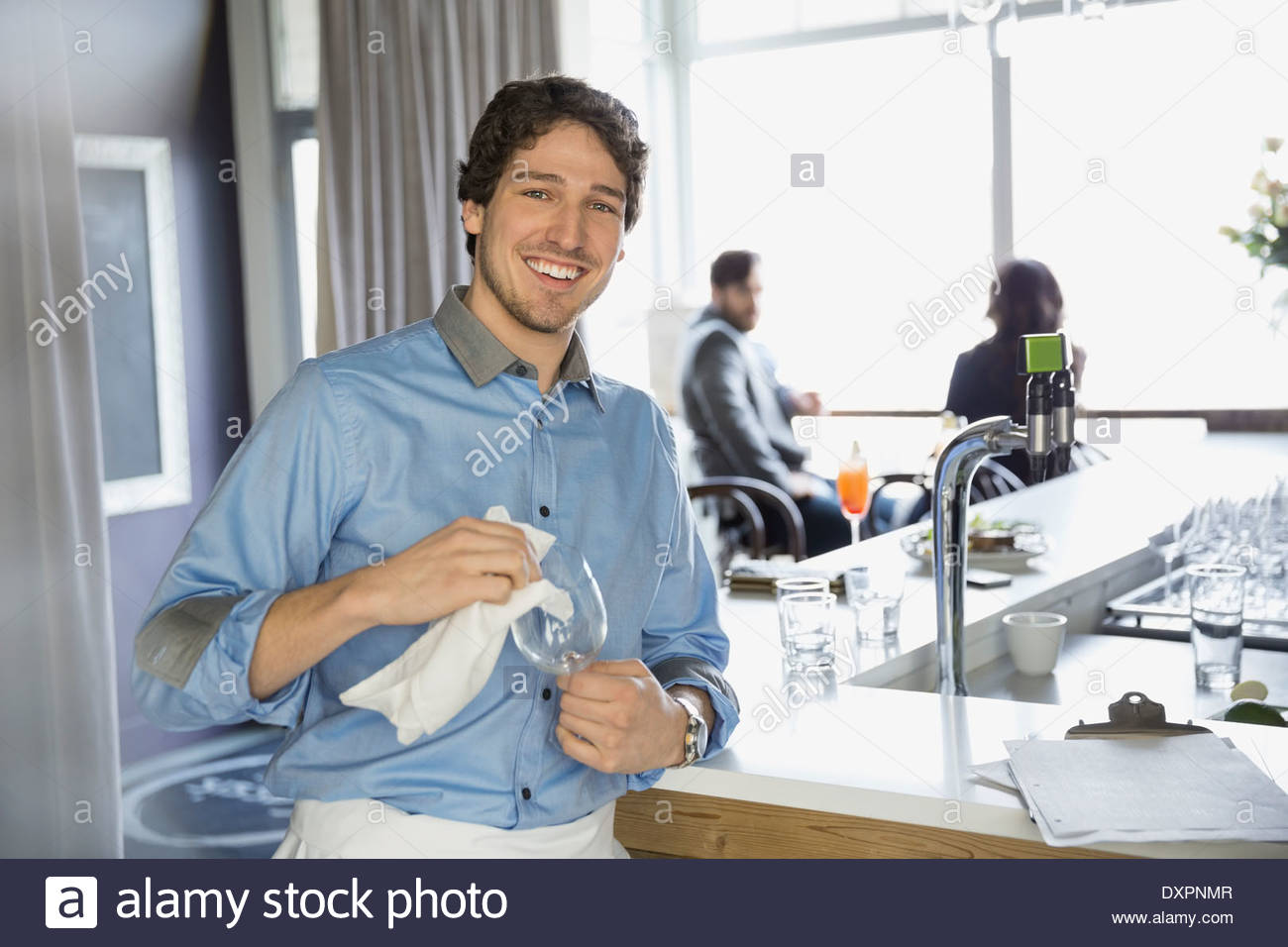 Portrait of bartender drying wine glass in bar - Stock Image
