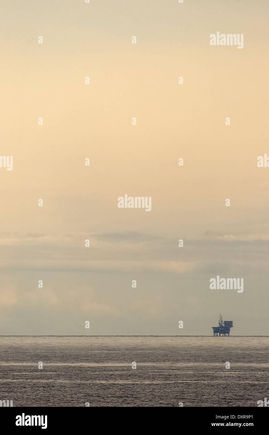 Single oil / gas rig far away on the horizon against a hazy evening sky. - Stock Image
