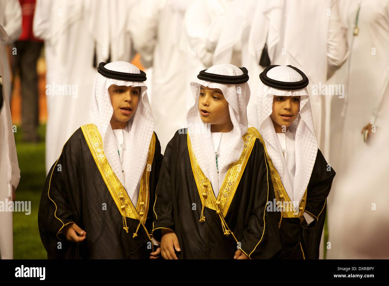 Meydan Racecourse, Dubai, UAE. 29th March, 2014. Three young princes greet the riders as they enter the parade ring - Stock Image