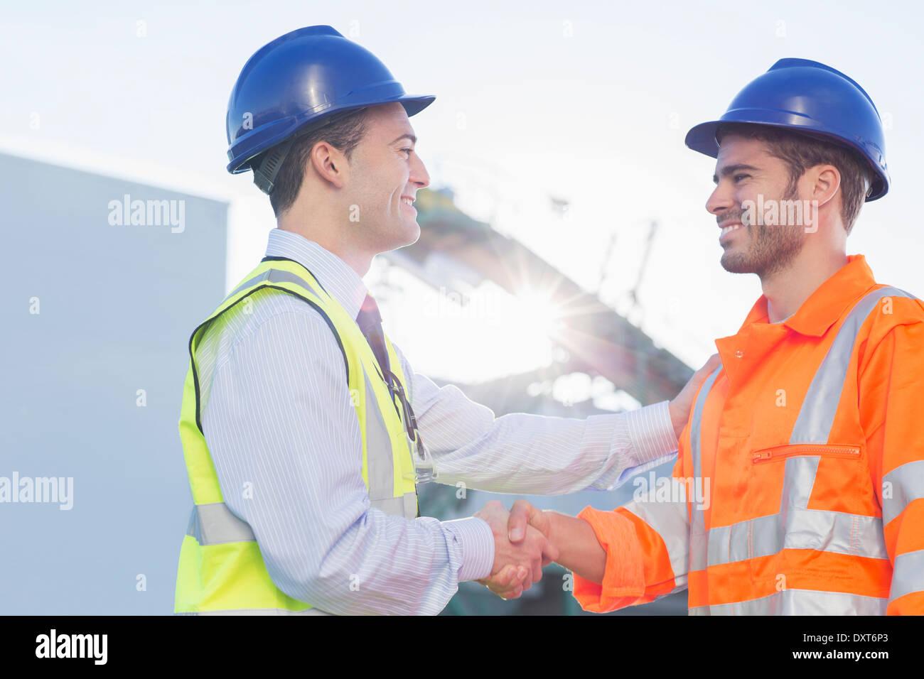 Businessman and worker handshaking - Stock Image