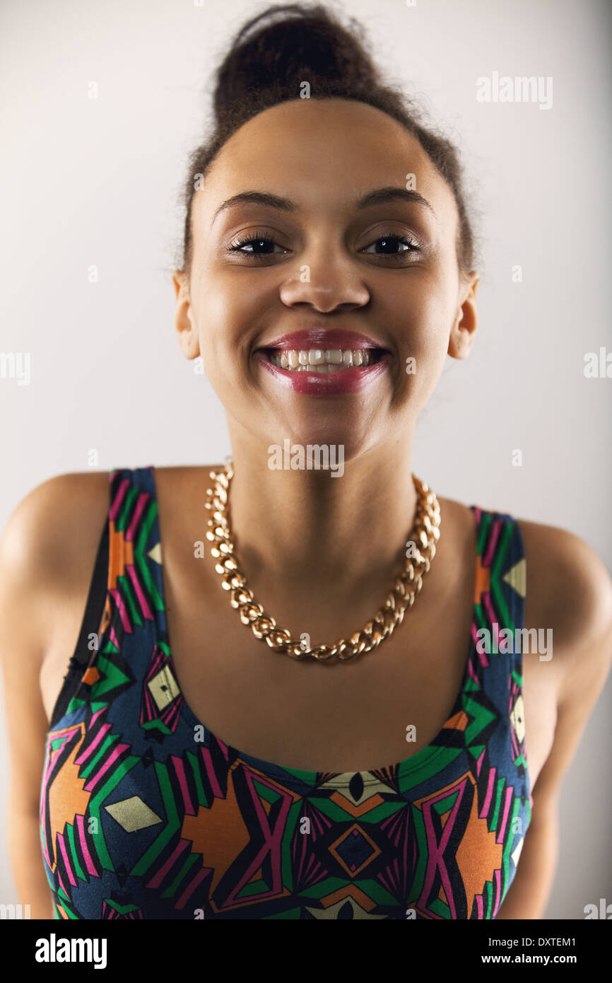 Close up portrait of pretty young woman making a funny face. Female model against grey background - Stock Image