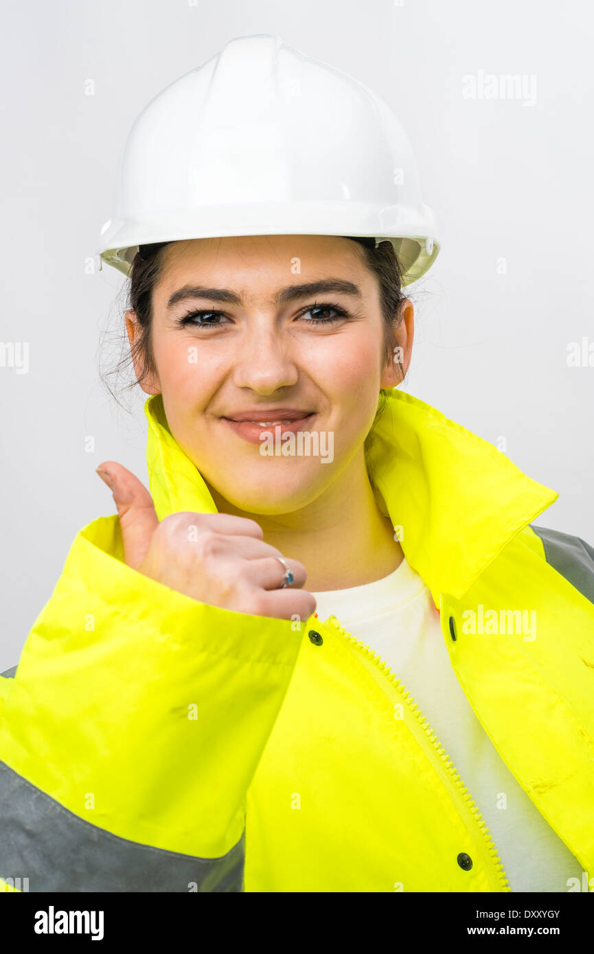 a young woman girl construction worker wearing hard hat and high vis