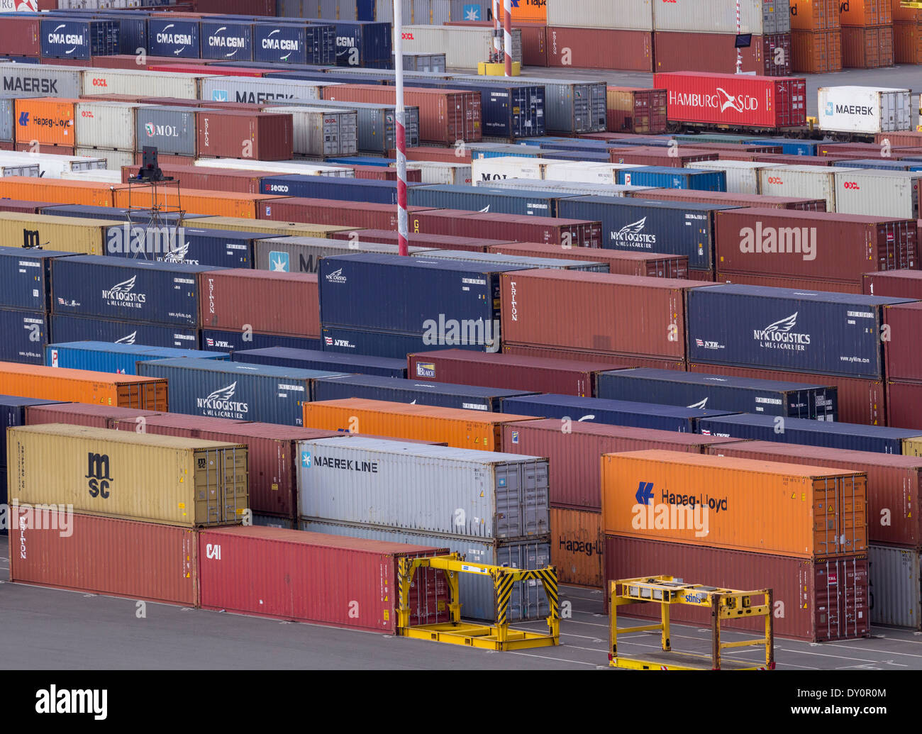 Stacks of industrial shipping containers by a wharf at a port - Stock Image