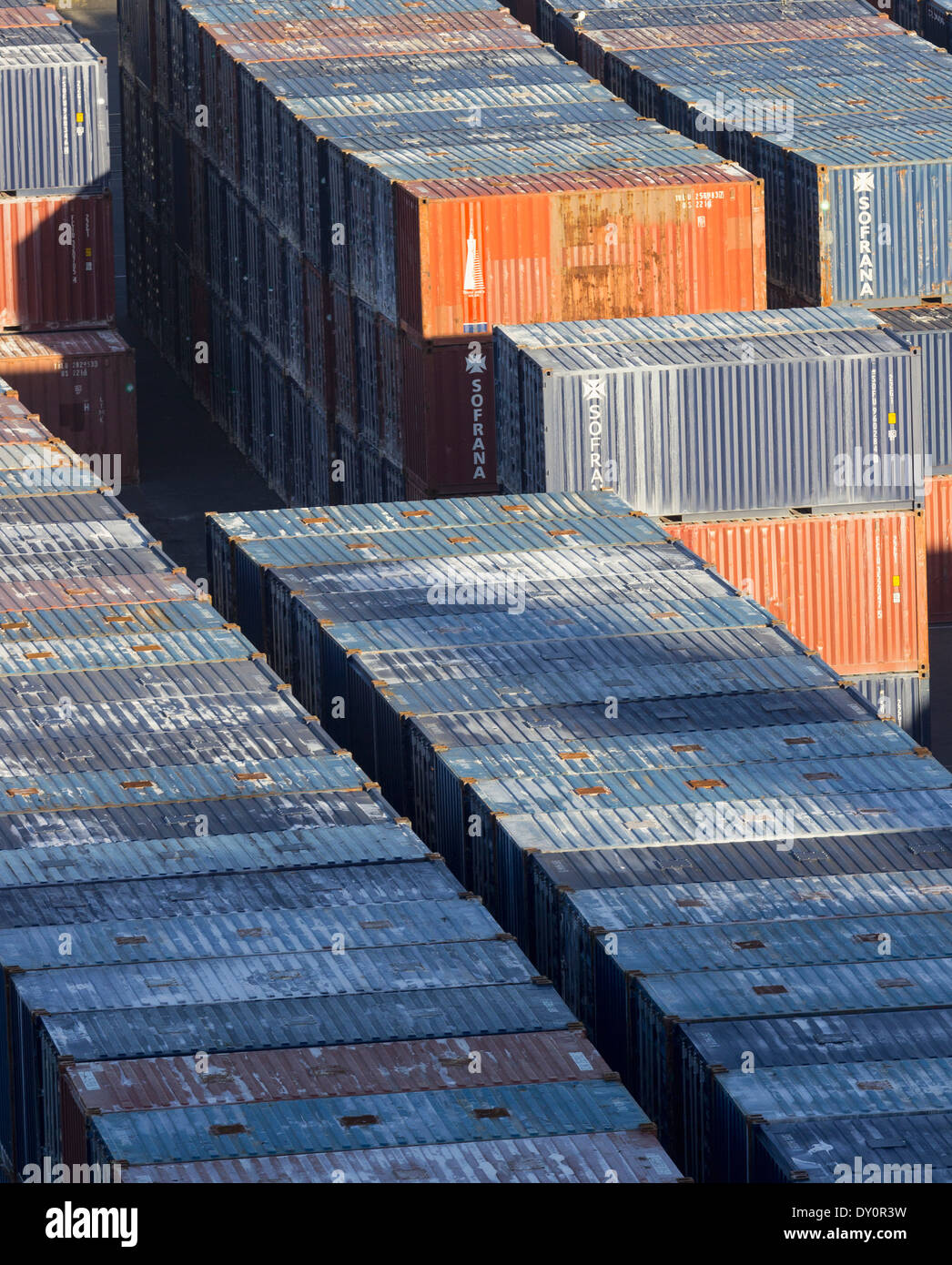 Stacks of industrial shipping containers at a port - Stock Image