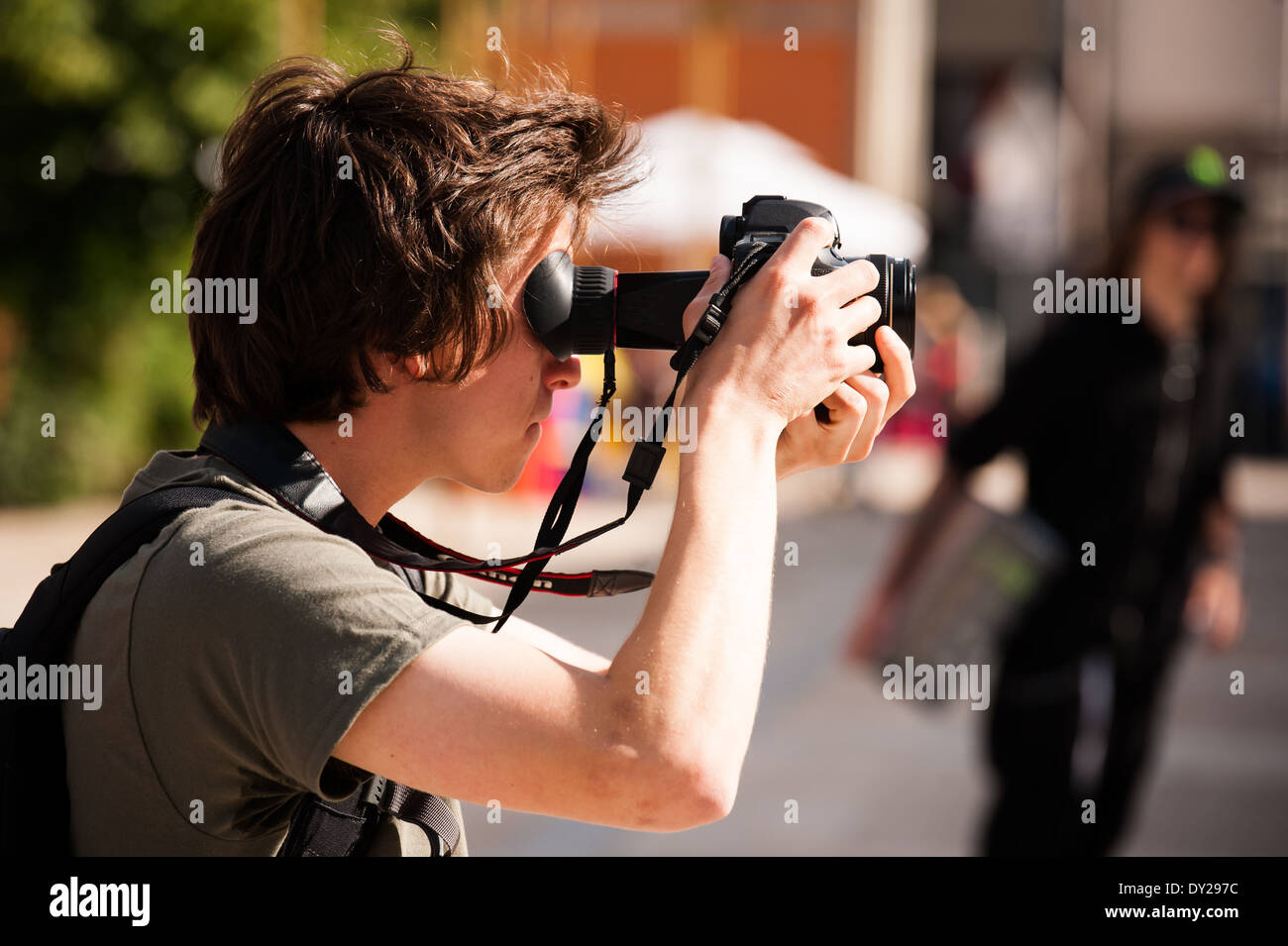 Man filming with a Canon DSLR camera, with his head close to the eye loupe - Stock Image
