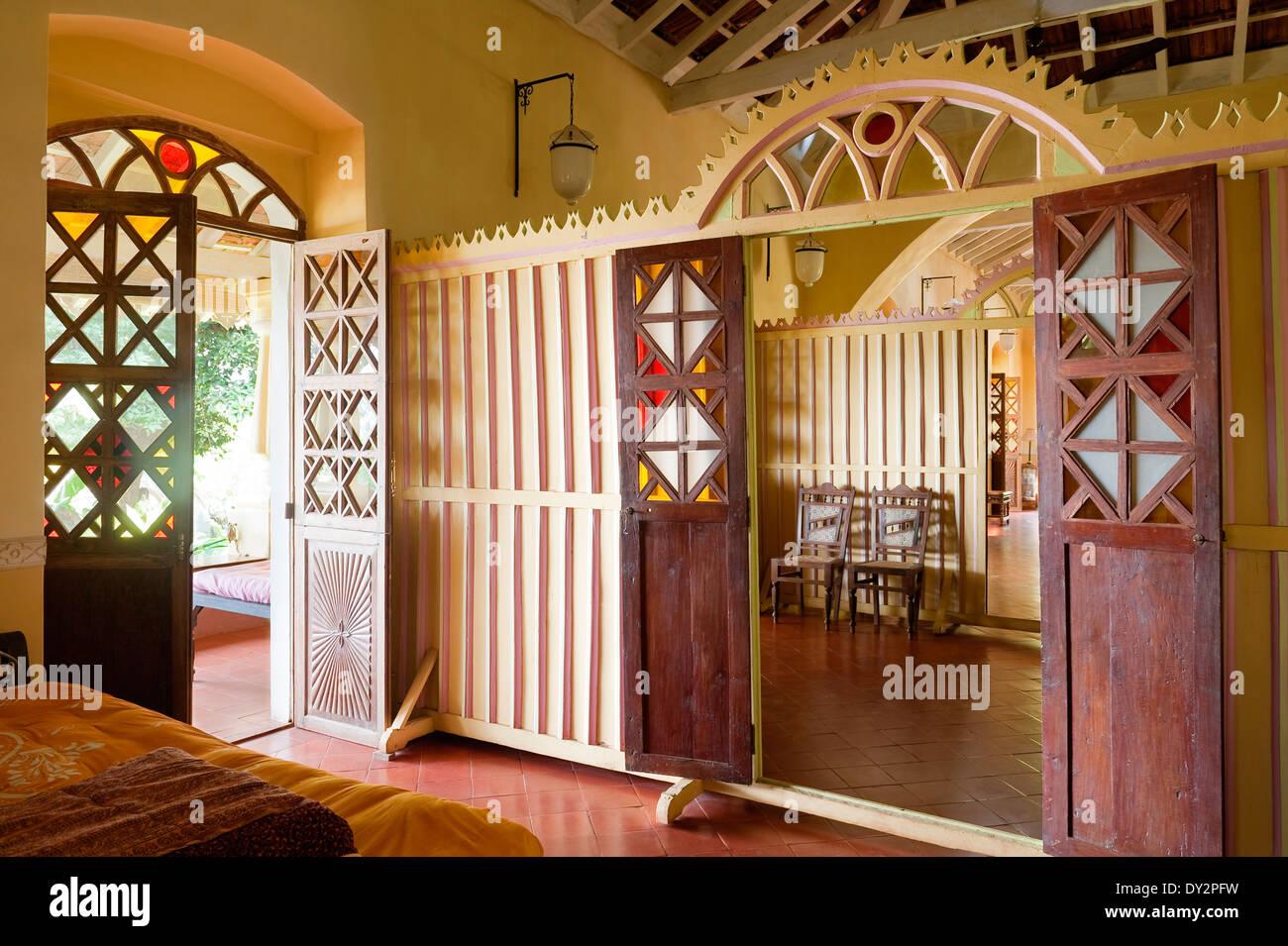 View through doorways of screen partition and door to veranda in Goan house India & View through doorways of screen partition and door to veranda in ...