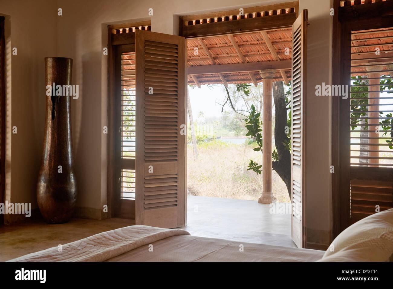 Double doors open from bedroom to veranda of Goan beach house retreat India & Double doors open from bedroom to veranda of Goan beach house Stock ...