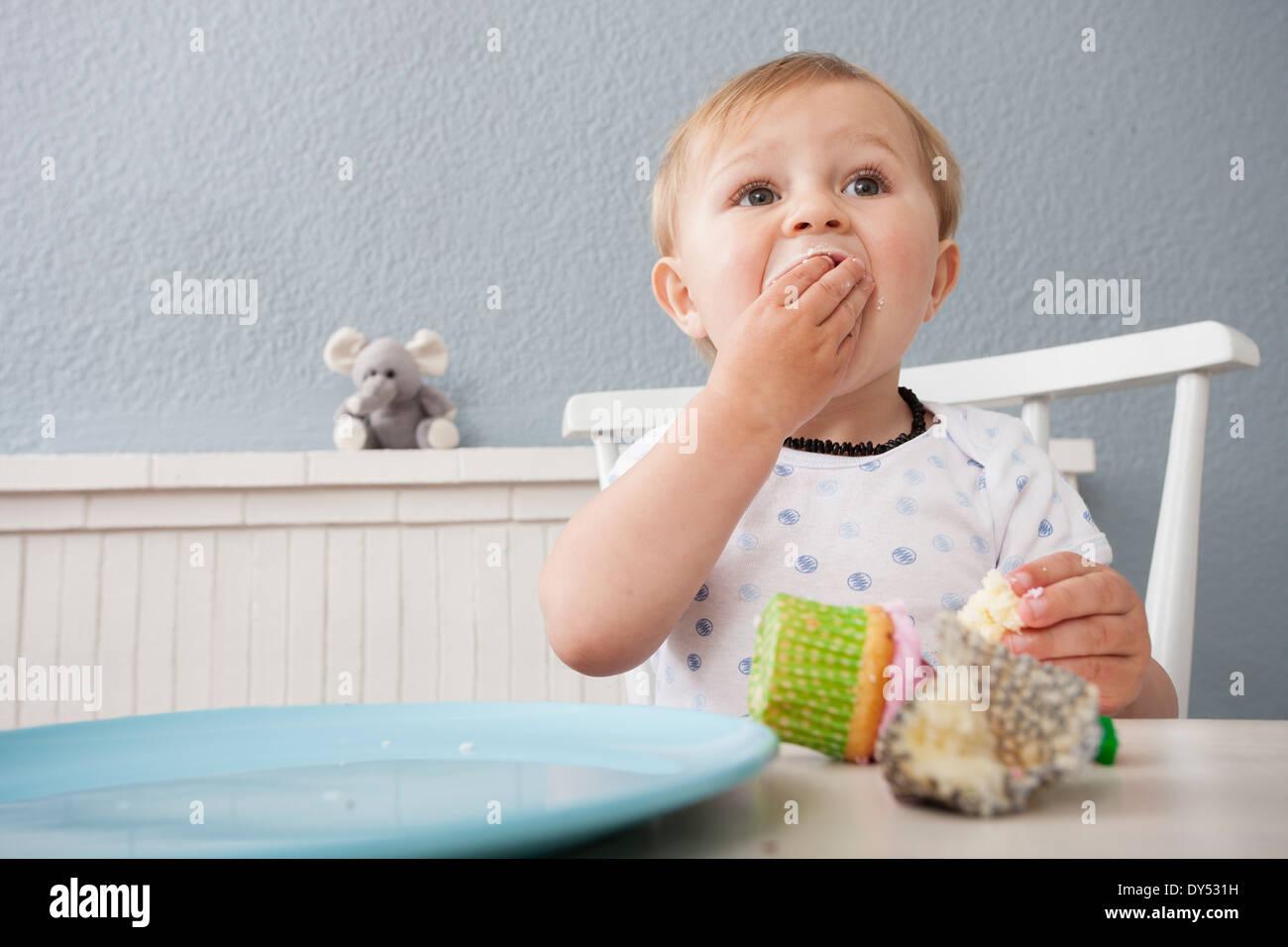 Baby boy eating cupcake - Stock Image