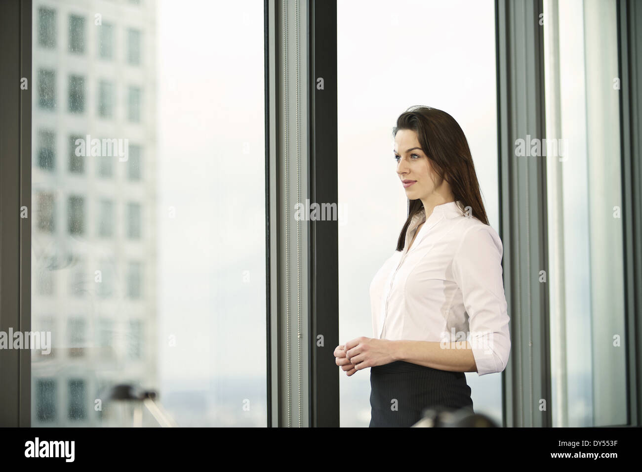 Portrait of businesswoman in high rise office - Stock Image