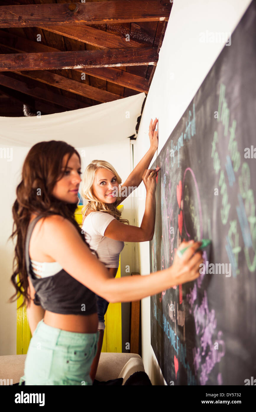 Young women drawing on blackboard - Stock Image