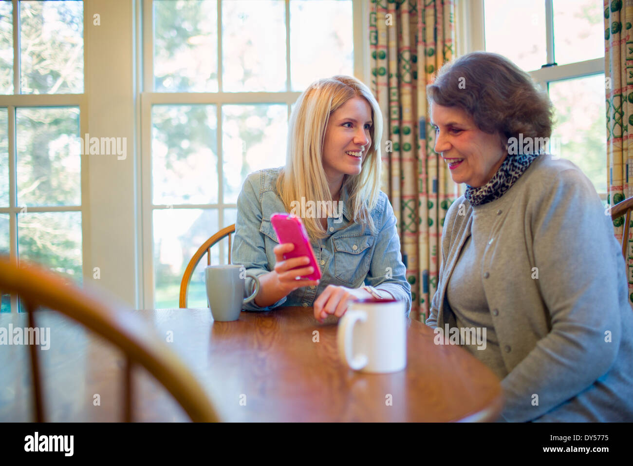 Senior woman and granddaughter looking at smartphone - Stock Image
