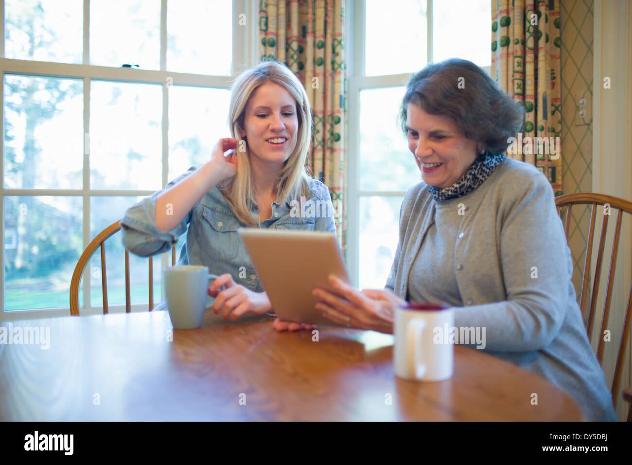 Senior woman and granddaughter looking at digital tablet - Stock Image