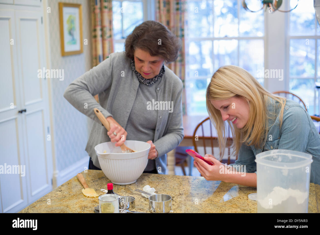 Senior woman and granddaughter baking and using cellphone - Stock Image
