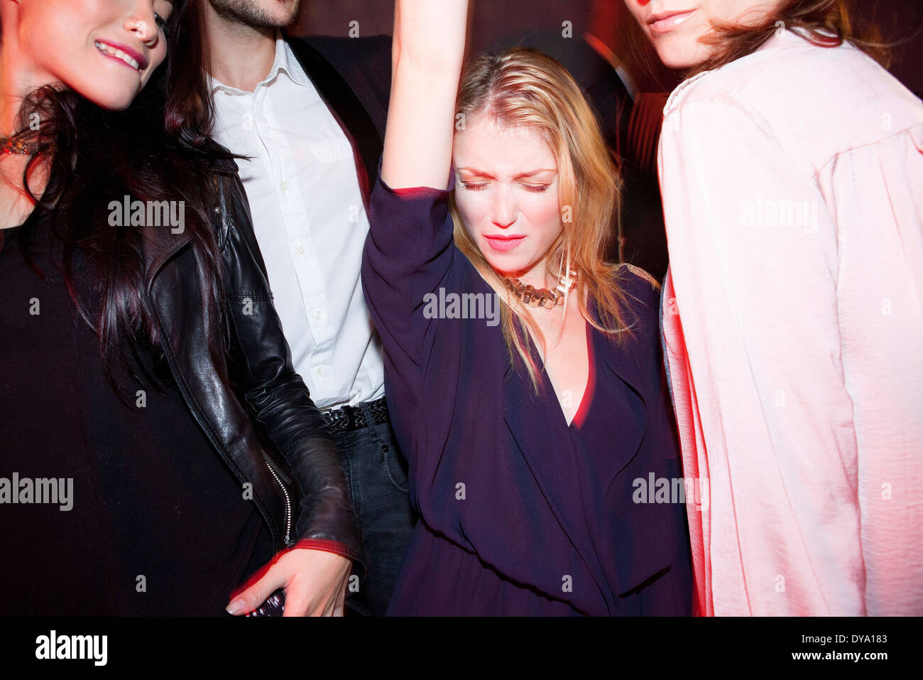 Young woman dancing with friends at night club - Stock Image