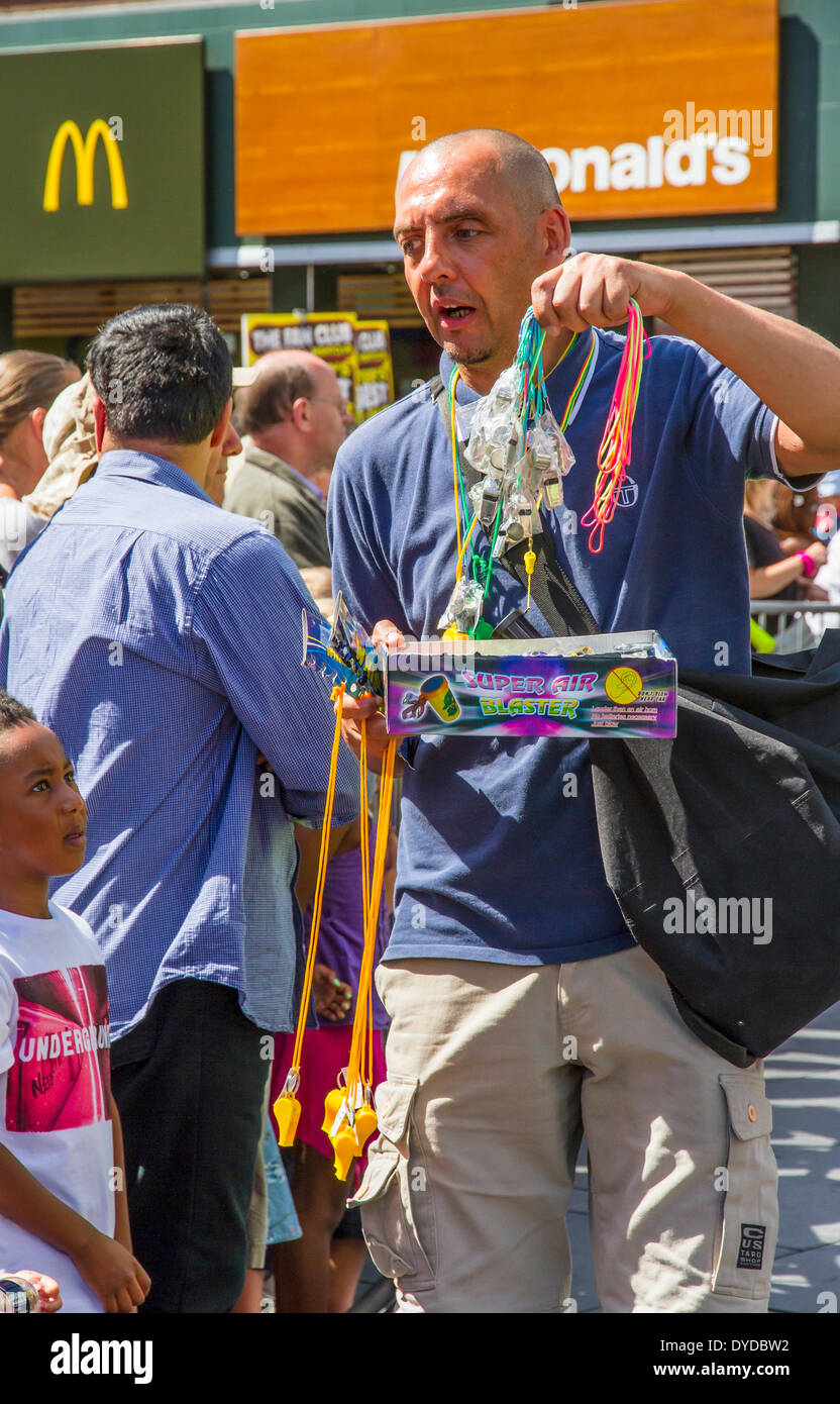 Street vendor selling whistles  at an event as a young boy looks hopefully. - Stock Image