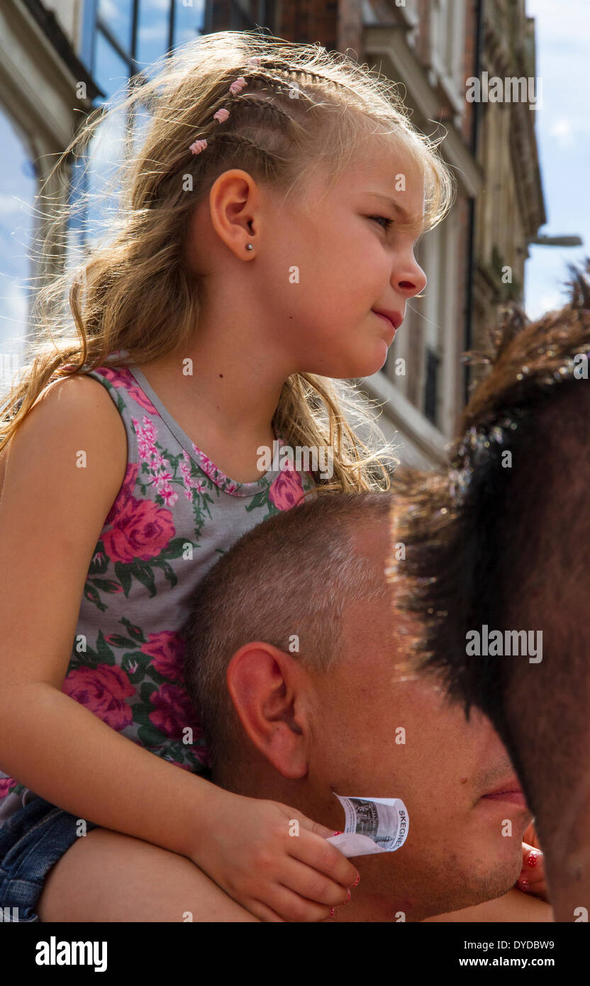 Young girl on her fathers shoulders so she can see the event. - Stock Image