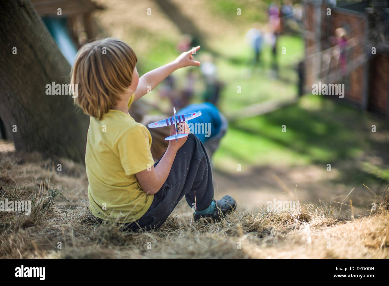 A young boy playing with a toy airplane at Hatfield House adventure playground. - Stock Image