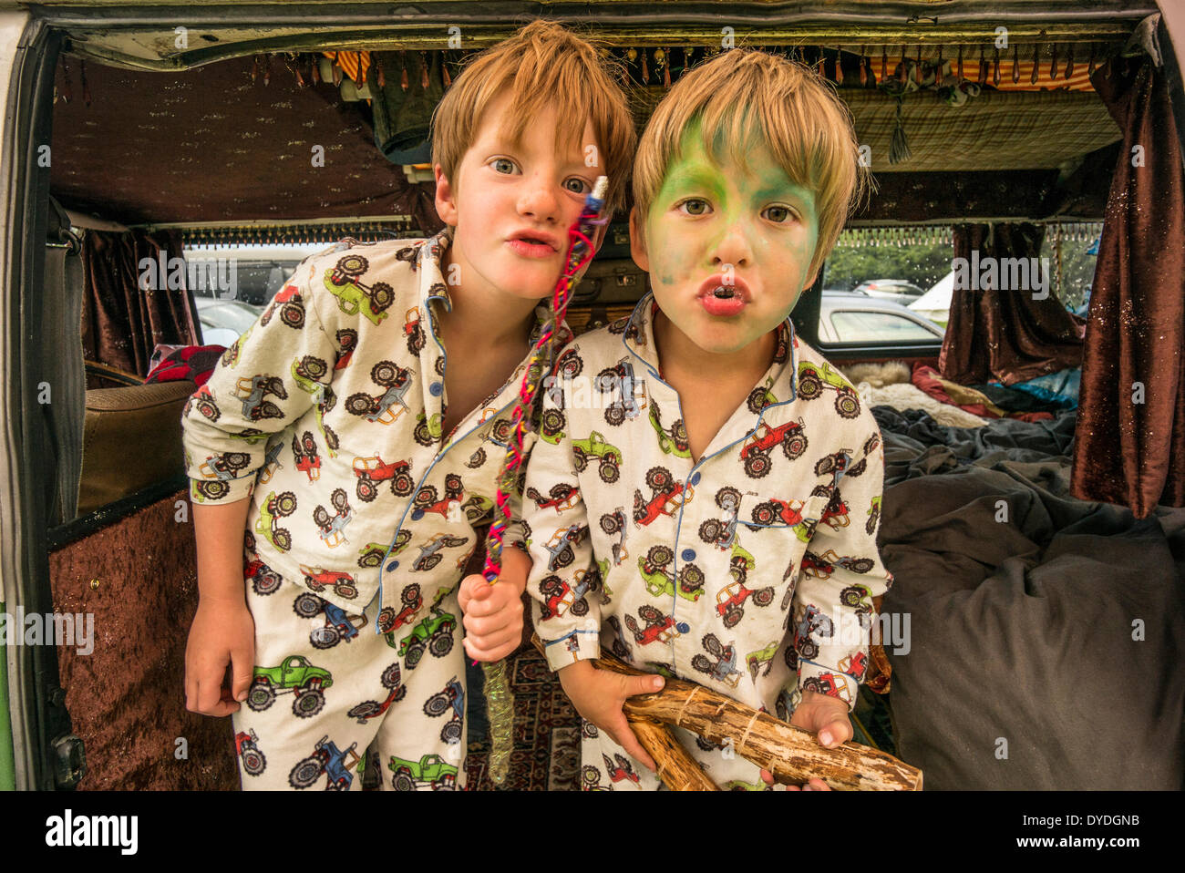Two boys having fun in a VW camper van  at a festival. - Stock Image