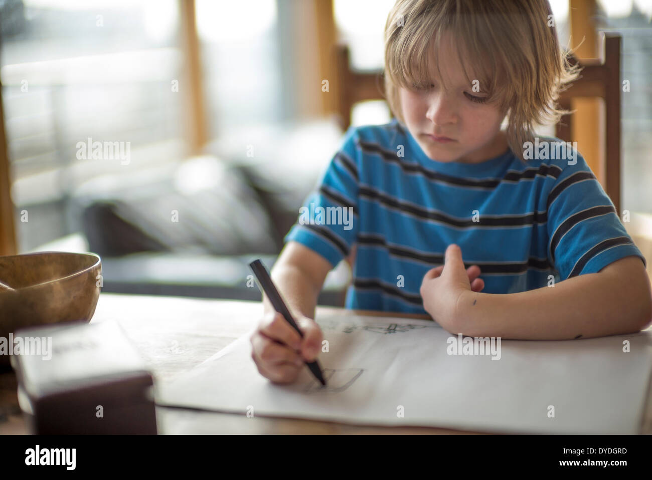 Seven year old boy drawing at the table. - Stock Image