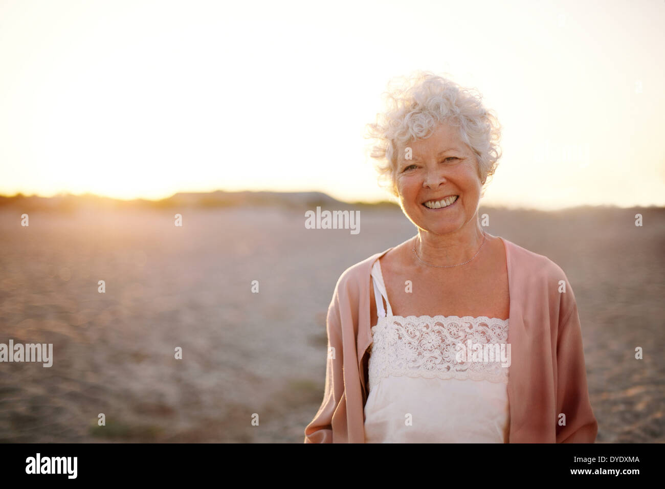 Portrait of cheerful old woman standing on the beach. Smiling senior caucasian female smiling outdoors. - Stock Image