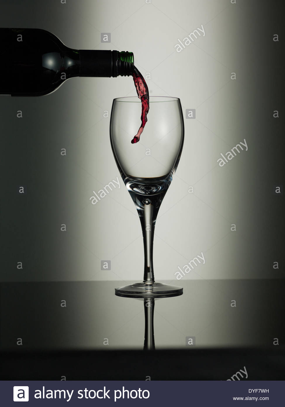 Red wine pouring into glass - Stock Image