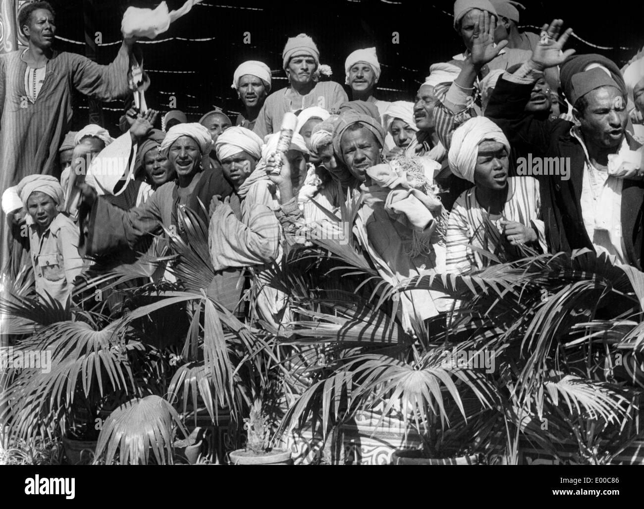 Men wait for the arrival of Gamal Abdel Nasser in Aswan - Stock Image