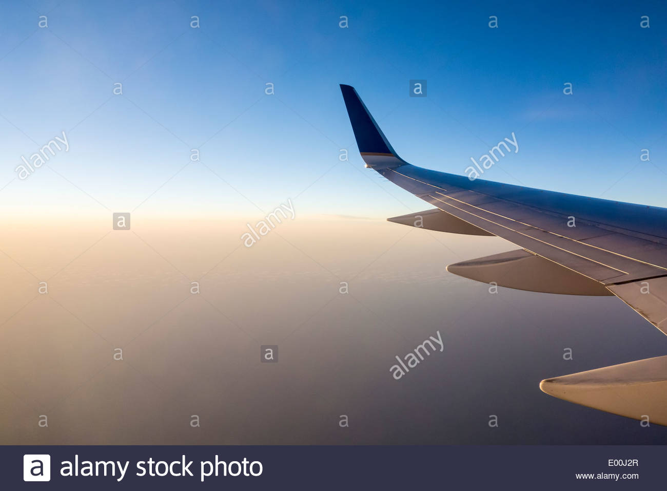 Passenger aircraft wing over the Pacific Ocean at sunset on the way to Los Angeles California USA Stock Photo