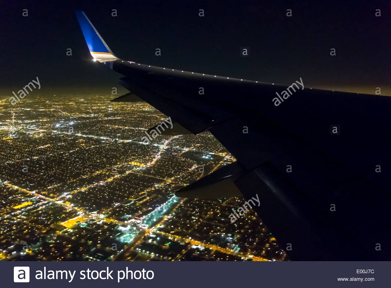 Passenger aircraft wing over Los Angeles approaching LAX at night Los Angeles California USAStock Photo