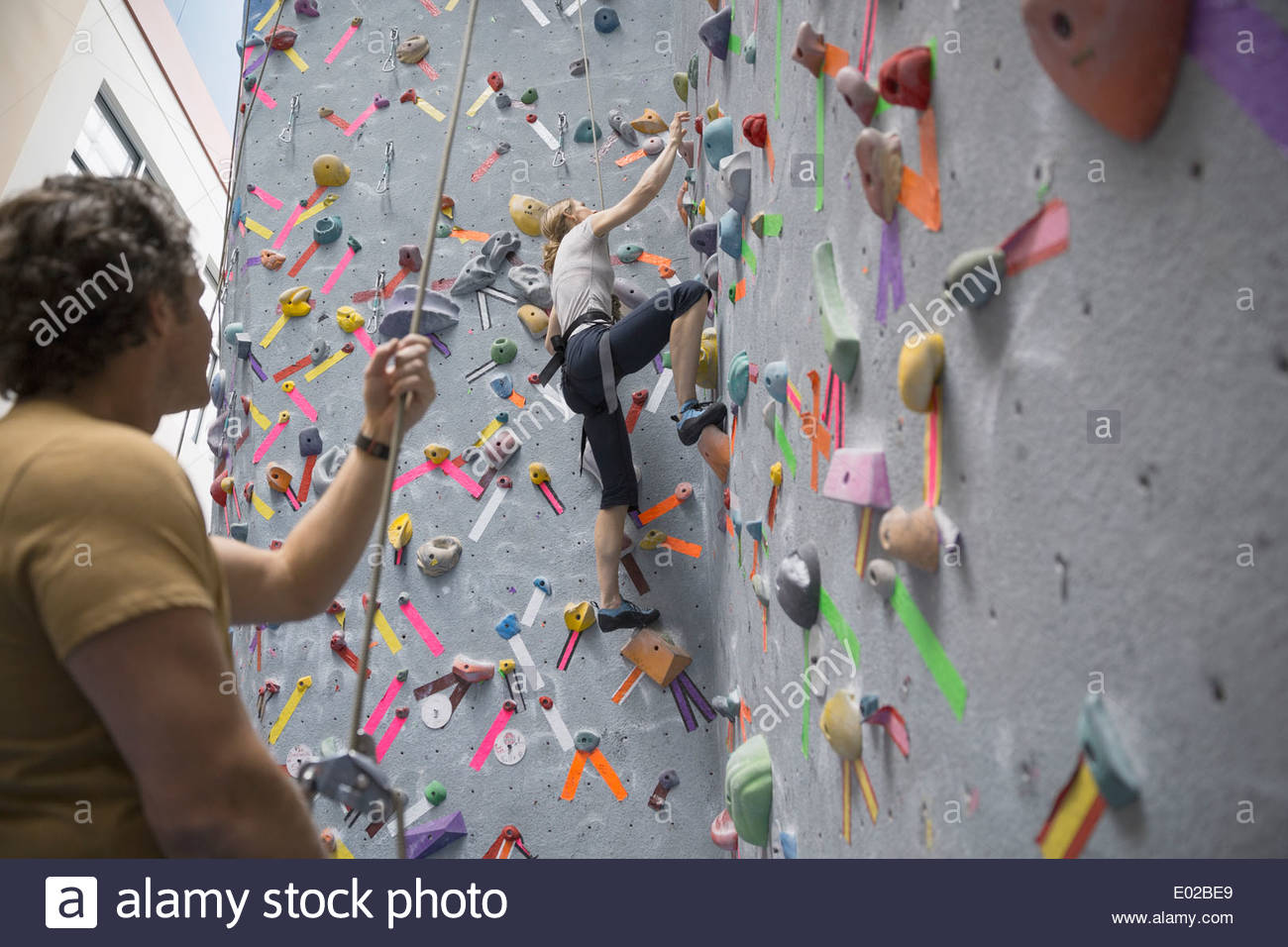 Man watching woman climb indoor rock wall - Stock Image