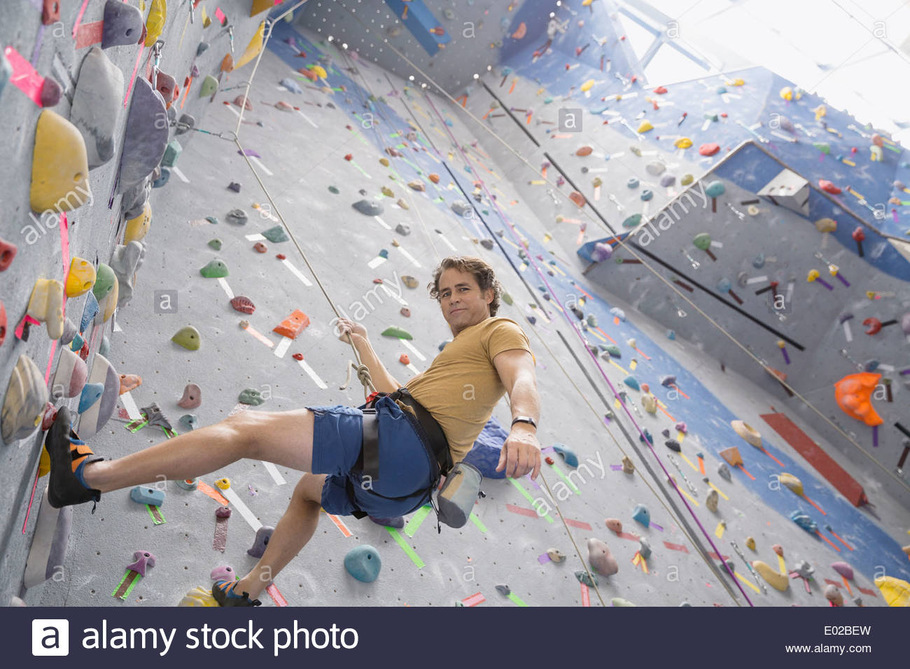 Portrait of man climbing indoor rock wall - Stock Image